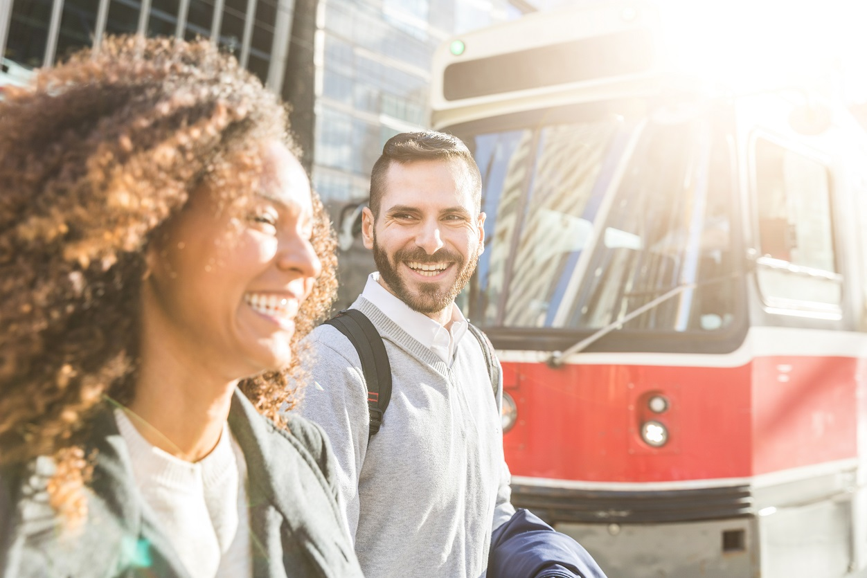 Commuters in the city walking and smiling with a streetcar on background. Modern business man and woman wearing smart casual clothes in the city. Urban lifestyle